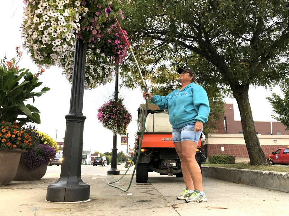 Up bright and early, Carla Wheeler spends her mornings watering the many flower baskets spread throughout the city of Big Rapids. Tuesday morning, the first official day of fall, was no different for Wheeler — a Big Rapids city worker — as she spent eight hours making sure the upkeep of the city's flowers was top notch. Photo: Pioneer Photo/Bradley Massman