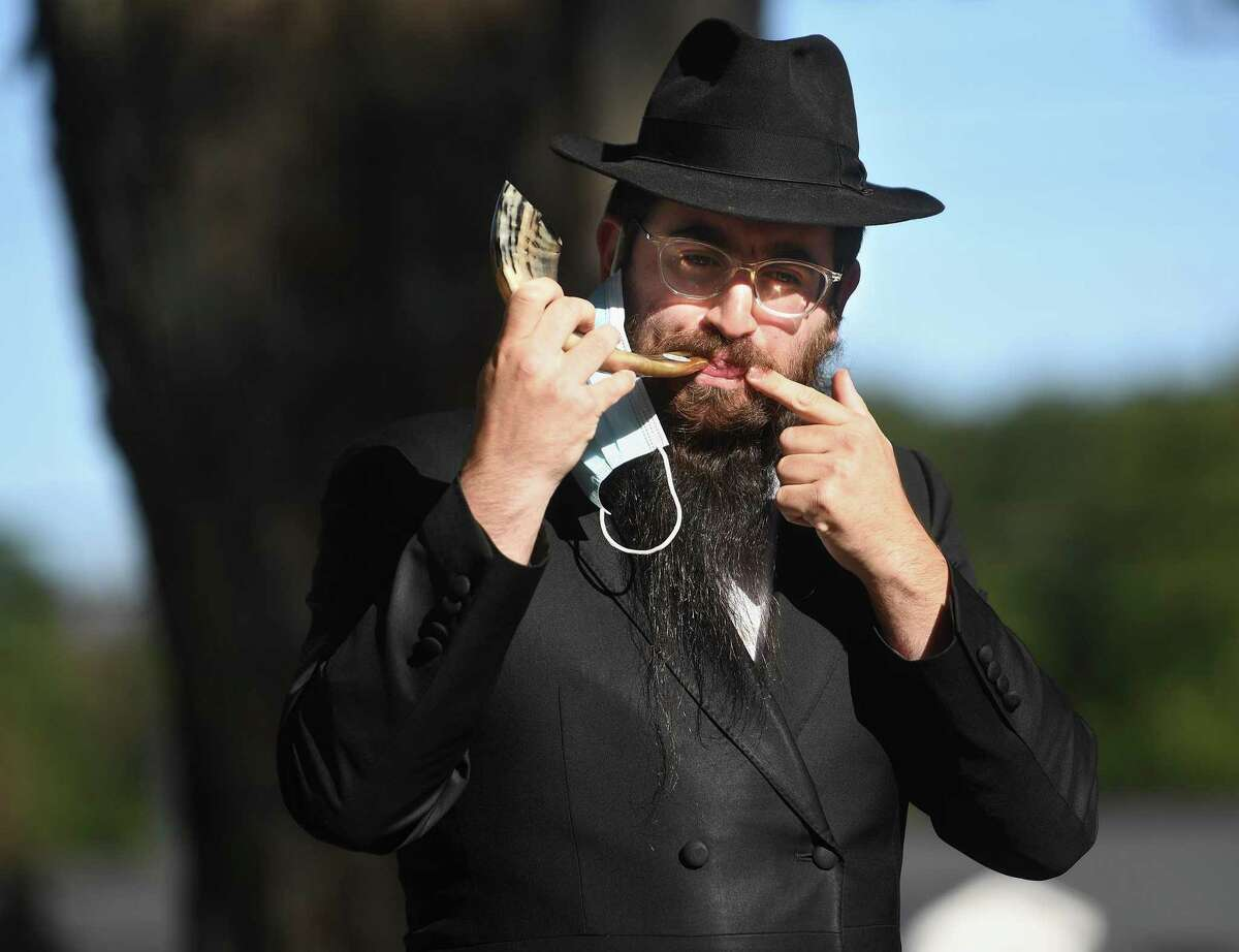 Rabbi Schneur Brook from Chabad of Shelton-Monroe blows the shofar during an outdoor Rosh Hashanah service on the Huntington Green in Shelton , Conn. on Sunday, September 20, 2020.