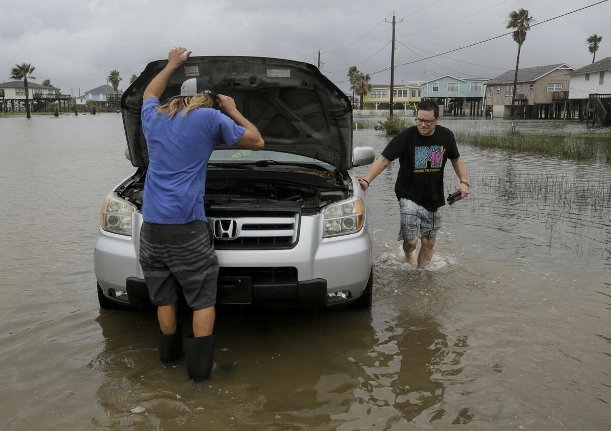 Austin Campbell, left, looks at the engine of Jeff Williams' car after getting it out of a flooded road Monday, Sept. 21, 2020, in Surfside, Texas. A tidal surge hit the island overnight, before Tropical Storm Beta makes landfall.