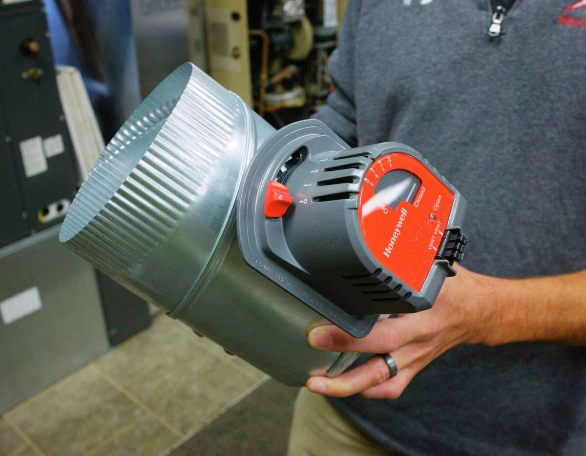 Jason Bethon, residential project manager at Albany Mechanical Services, holds a fresh air intake damper at the company's showroom on Thursday, Sept. 17, 2020, in Green Island, N.Y. The unit would be added to a home to bring fresh air into a home that is insulated and sealed up. (Paul Buckowski/Times Union)