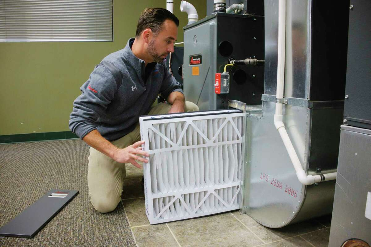 Jason Bethon, residential project manager at Albany Mechanical Services, slides a merv 8 filter back into the holder on the furnace at the company's showroom on Thursday, Sept. 17, 2020, in Green Island, N.Y. (Paul Buckowski/Times Union)
