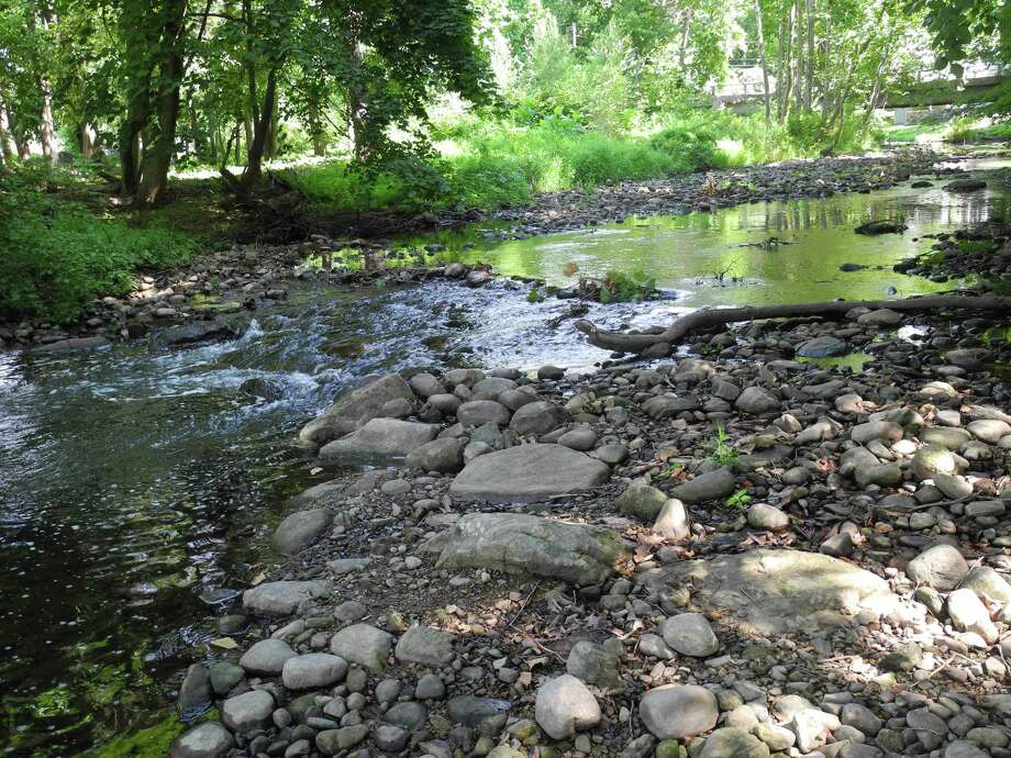 Rocks that normally would be under water are high and dry along the Norwalk River as it flows through Schenck's Island on Aug. 21, 2020, in Wilton, Conn. Norwalk, along with other Fairfield County communities, is experiencing a water emergency. Photo: Jeannette Ross / Hearst Connecticut Media / Wilton Bulletin
