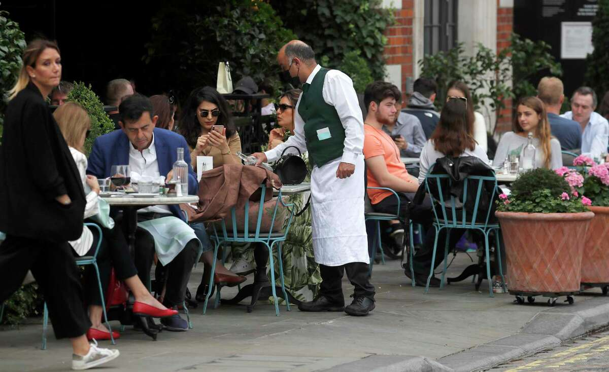 A waiter serves in a restaurant in Covent Garden in London, Tuesday, Sept. 22, 2020. Either a sufficient portion of the world's population contracts the virus and survives (which is not good, considering the lingering effects of even moderate COVID-19 infections) or a vaccine is proven safe and effective and is distributed widely. You should probably imagine regular, yearly or seasonal immunizations, like we get for the flu, so