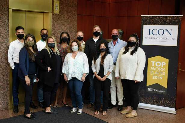 ICON International employees pose at the company's headquarters in Greenwich, Conn. Wednesday, Sept. 16, 2020. The specialized finance company focuses on corporate barter transactions.
