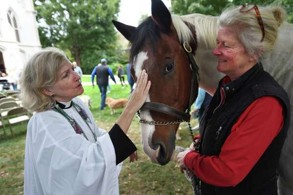 Rev. Peggy Hodgkins, left, says a blessing for Artie, a horse belonging to Durell Green, of Easton, at the annual Blessing of the Animals service last October at Trinity Episcopal Church in Southport. This year's event is Oct. 4.