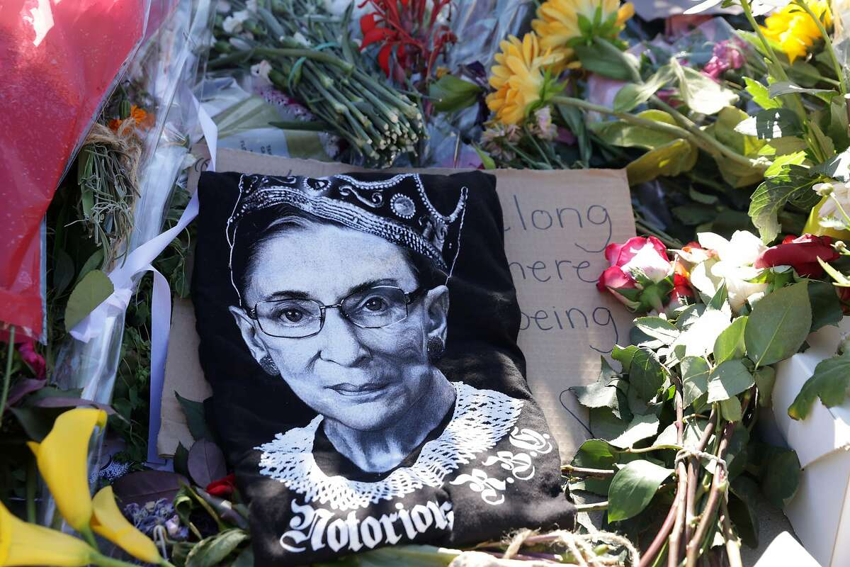 Signs and flowers are left at a makeshift memorial in front of the U.S. Supreme Court for the late Justice Ruth Bader Ginsburg September 21, 2020 in Washington, D.C. The voter, Doreen Lawson, reportedly complied when she was asked to zip her jacket over the