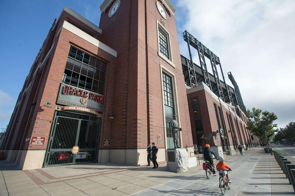 A pair of San Francisco Giants fans ride past Oracle Park just before the first pitch of the Giants home opener against the San Diego Padres at Oracle Park in San Francisco on July 28, 2020.