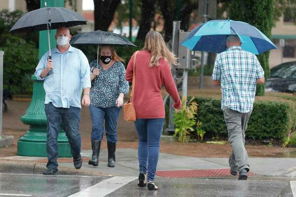 Robert Cummings and his wife, Amy, make their way across West Davis Street as rainbands from Tropical Storm Beta make their way though Montgomery County, Tuesday, Sept. 22, 2020, in Conroe. The county is expected to recieve additional rainfall from Beta through Wednesday.