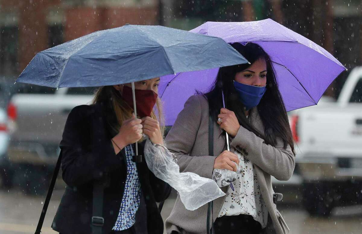 Two women, who wished not to be identifed, make their way across West Davis Street as rainbands from Tropical Storm Beta make their way through Montgomery County, Tuesday, Sept. 22, 2020, in Conroe. The county is expected to receive additional rainfall from Beta through Wednesday.