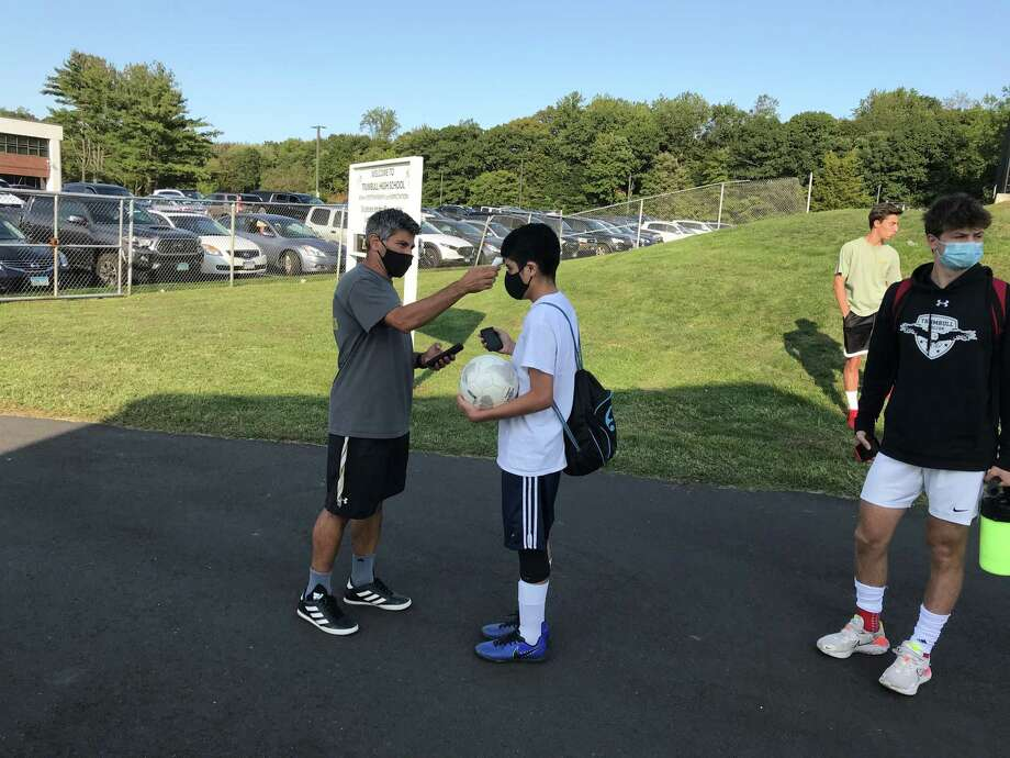 Trumbull boys soccer coach Sil Vitiello takes a players temperature before practice. Photo: Bill Bloxsom / HearstMediaCt / Trumbull Times