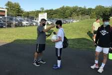 Trumbull boys soccer coach Sil Vitiello takes a players temperature before practice.