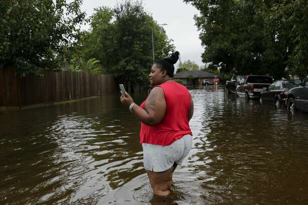Brenda Duckworth walks on Wingtip Drive, checking the extend of the flooding in her neighborhood due to Tropical Storm Beta on Tuesday, Sept. 22, 2020, in Houston.