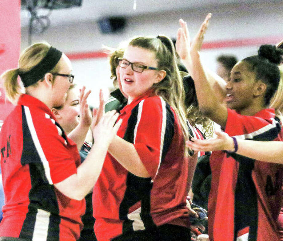 Alton High bowler Alex Bergin, center, in congratulated by teammates at a IHSA Girls Bowling Regional Tourney at Bowl Haven. Because of COVID-19 regulations, the number of bowlers and spectators will be limited when teams begin their winter season begins. Photo: Pete Hayes | The Telegraph