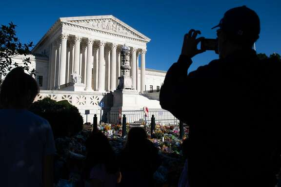 CORRECTION - A visitor takes photos near a makeshift memorial for late US Supreme Court Justice Ruth Bader Ginsburg at the US Supreme Court in Washington, DC, September 21, 2020. - Ruth Bader Ginsburg will lie in repose at the Supreme Court on September 23 and September 24, 2020, before lying in state on September 25, 2020 at the US Capitol, both institutions announced. The late justice, whose death at age 87 has given President Donald Trump a rare chance to cement a conservative majority on the court, will be buried next week in a private ceremony in Arlington, near the US capital. (Photo by SAUL LOEB / AFP) / The erroneous mention[s] appearing in the metadata of this photo by SAUL LOEB has been modified in AFP systems in the following manner: [Ginsburg] instead of [Ginsberg]. Please immediately remove the erroneous mention[s] from all your online services and delete it (them) from your servers. If you have been authorized by AFP to distribute it (them) to third parties, please ensure that the same actions are carried out by them. Failure to promptly comply with these instructions will entail liability on your part for any continued or post notification usage. Therefore we thank you very much for all your attention and prompt action. We are sorry for the inconvenience this notification may cause and remain at your disposal for any further information you may require. (Photo by SAUL LOEB/AFP via Getty Images)