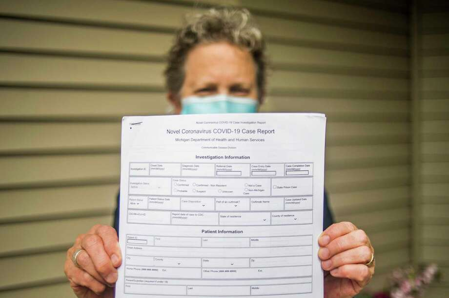 Mary MacInnes, clinical services director for the Midland County Department of Public Health, holds up a coronavirus case report form Tuesday, Sept. 22, 2020 at her home in Saginaw. (Katy Kildee/kkildee@mdn.net)