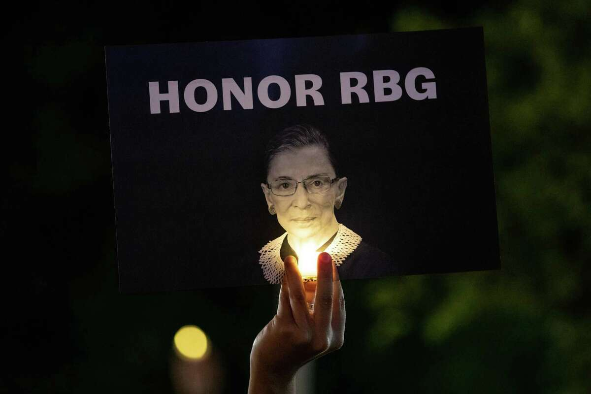 A mourner holds up a sign at a makeshift memorial during a vigil for Supreme Court Justice Ruth Bader Ginsburg in Washington, D.C., on Saturday. Several readers have said Ginsburg should be remembered and grieved before political questions take prominence.