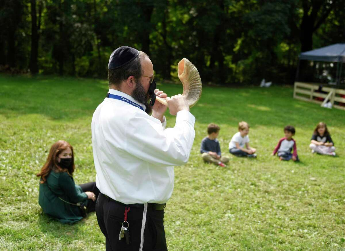 Rabbi Yossi Deren blows the shofar at the new Jewish school Tamim Academy in Greenwich, Conn. Tuesday, Sept. 15, 2020. Located at the location of the former Carmel Academy, the new school is an affiliate of Chabad Lubavitch Greenwich for preschool and kindergarten students.