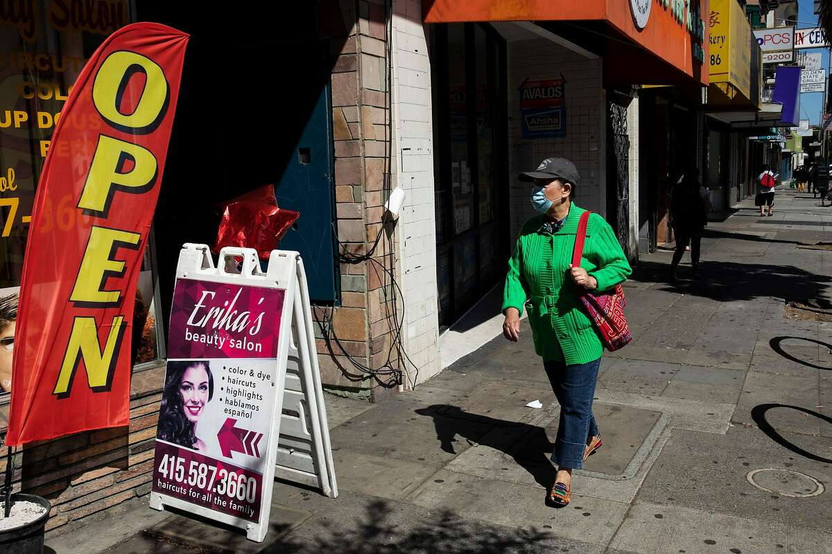 A person walks past a beauty salon along Mission Street in the Excelsior District, Tuesday, Sept. 22, 2020, in San Francisco, Calif. The death toll of the coronavirus pandemic in the U.S. surpassed 200,000.