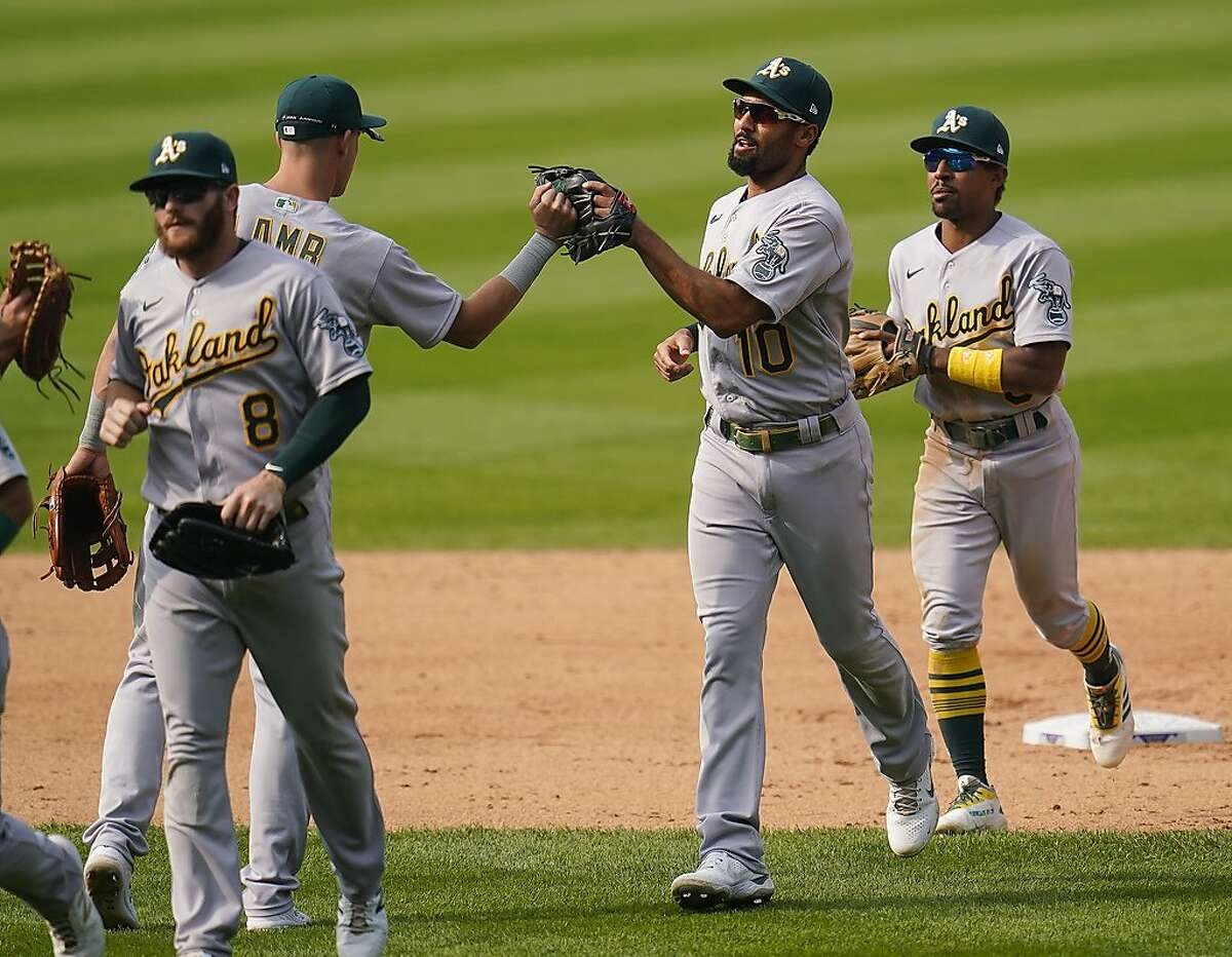 Oakland Athletics shortstop Marcus Semien (10) and teammates celebrate a win against the Colorado Rockies in a baseball game Wednesday, Sept. 16, 2020, in Denver. (AP Photo/Jack Dempsey)
