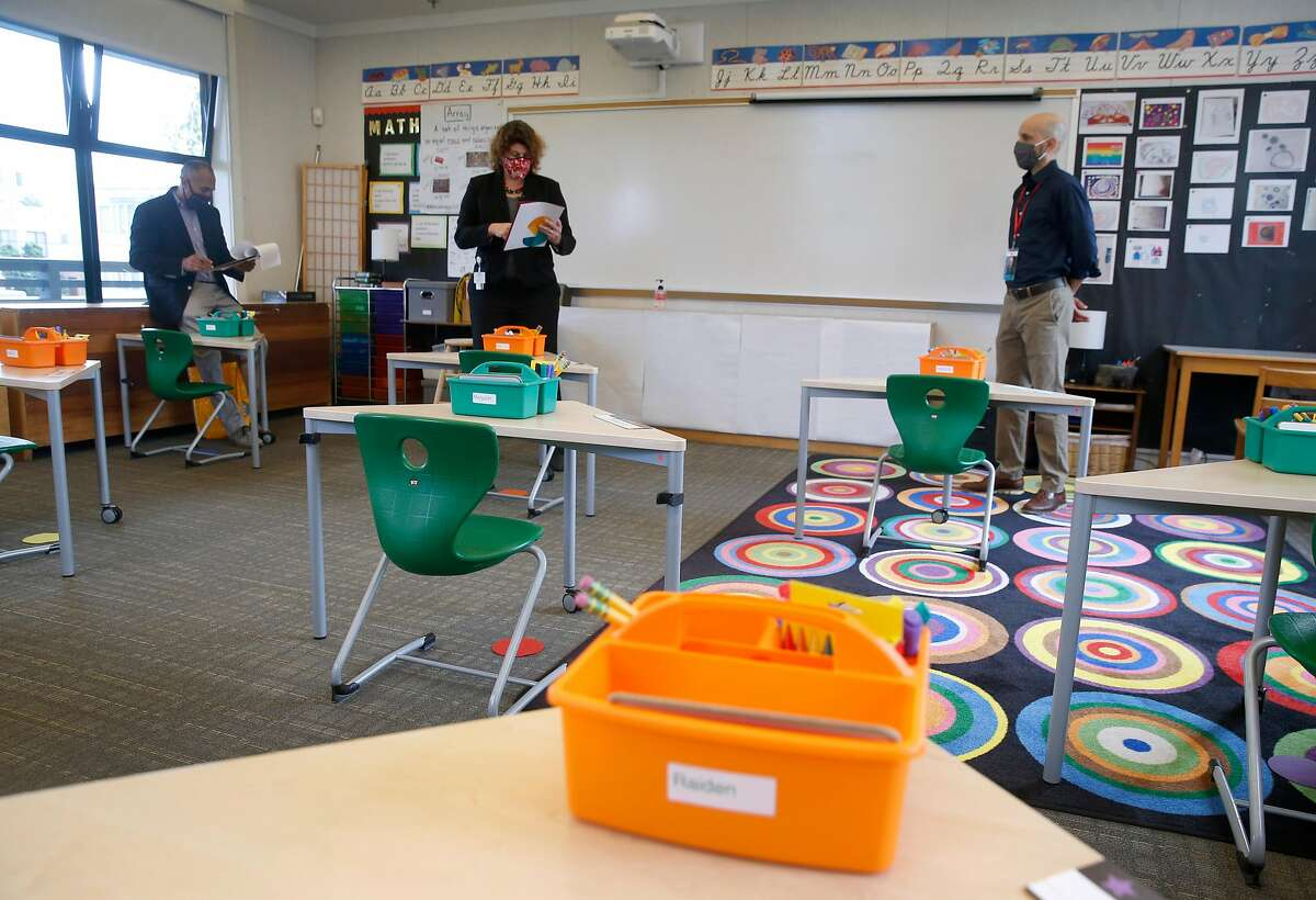 Head of School Steve Morris (right) leads a tour of a classroom for city inspectors Julian Vanales (left) and Ana Validzic at The San Francisco School before authorizing in-person learning on the campus in San Francisco, Calif. on Thursday, Sept. 17, 2020. The private school with 285 students enrolled is among the first school's in the city to apply for in-classroom instruction.
