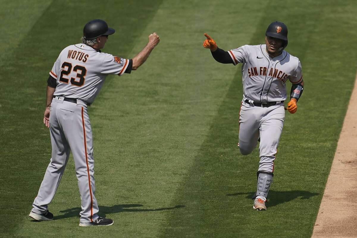 San Francisco Giants' Chadwick Tromp, right, celebrates with third base coach Ron Wotus after hitting a two-run home run against the Oakland Athletics during the third inning of a baseball game in Oakland, Calif., Sunday, Sept. 20, 2020. (AP Photo/Jeff Chiu)