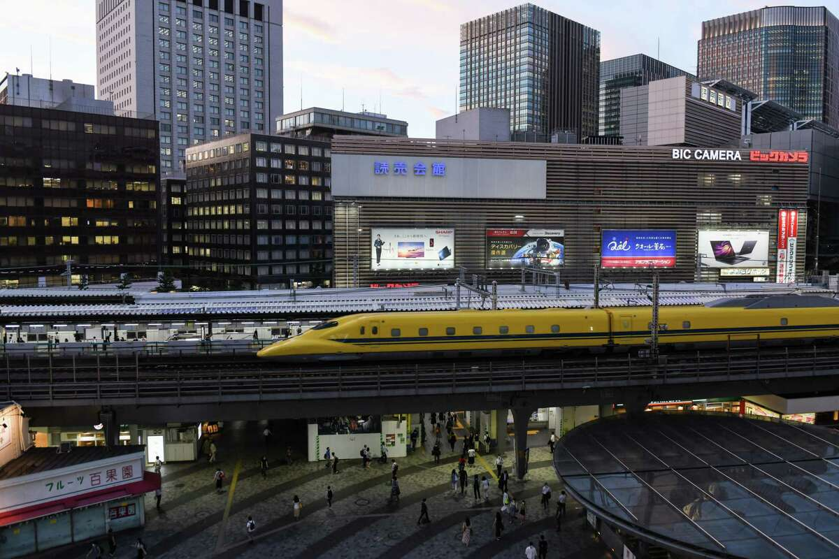 A 'Doctor Yellow' Shinkansen bullet train, a high-speed test train to monitor the condition of tracks and overhead wires, travels along an elevated railway track passing Yurakucho station in Tokyo, Japan, on Tuesday, Sept. 8, 2020. In Tokyo, the spaces beneath elevated railways are more than just storage and parking. They are agglomerations of cozy restaurants and shops that are intimately tied to the identity of certain commercial districts.