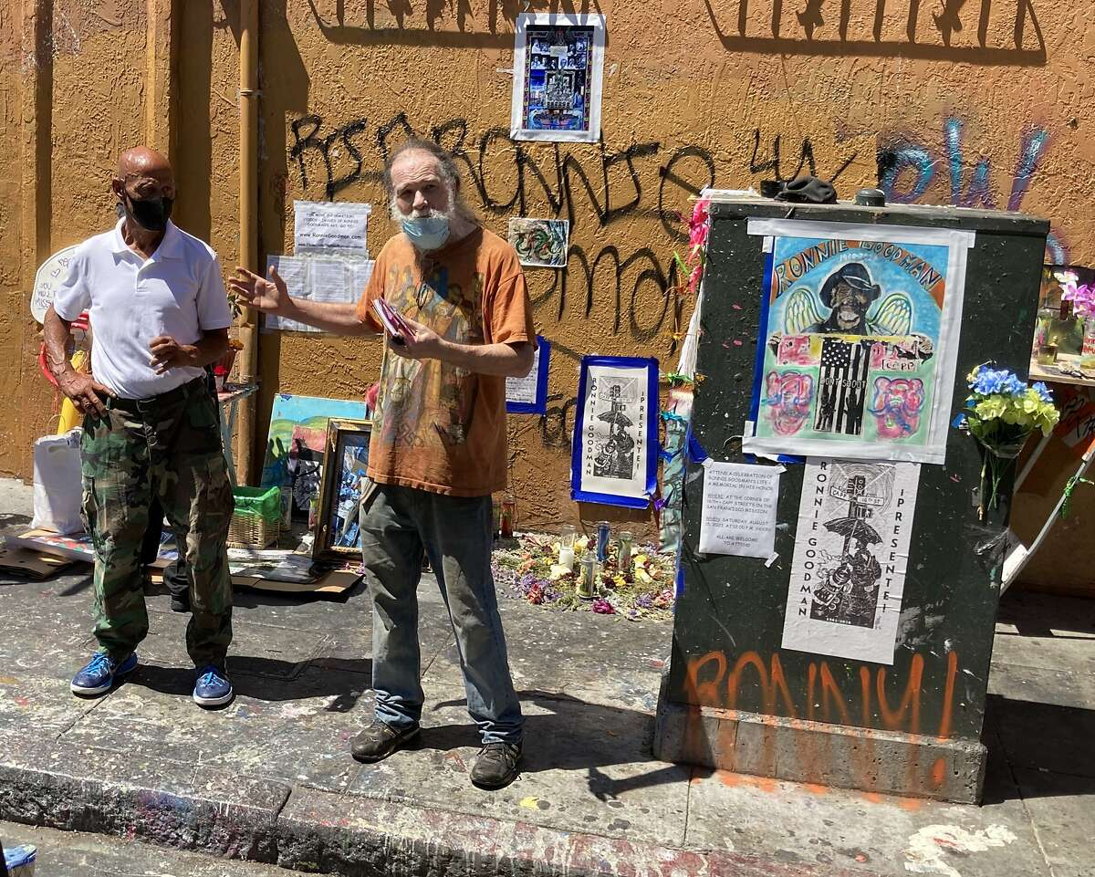 """""""Coach,"""" left, and Roger Herried pay tribute at an Aug. 15, 2020 memorial for their friend San Francisco homeless artist Ronnie Goodman, who died Aug. 7 at the corner they are standing at, 16th and Capp streets. Goodman's art is in a New York MoMA PS1 exhibit that opened in September 2020, """"Marking Time: Art in the Age of Mass Incarceration."""""""