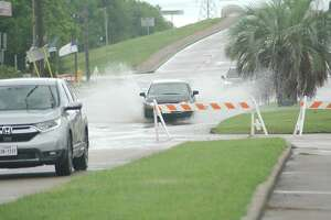 A barricade warns commuters of high water heading westbound on Scarsdale Boulevard near the Gulf Freeway during Tropical Storm Beta.