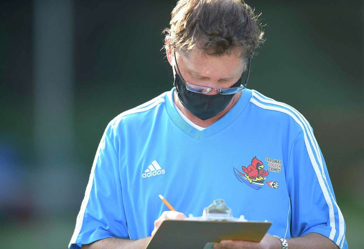 Greenwich boys soccer coach Kurt Putnam wears a protective face covering as he takes notes .