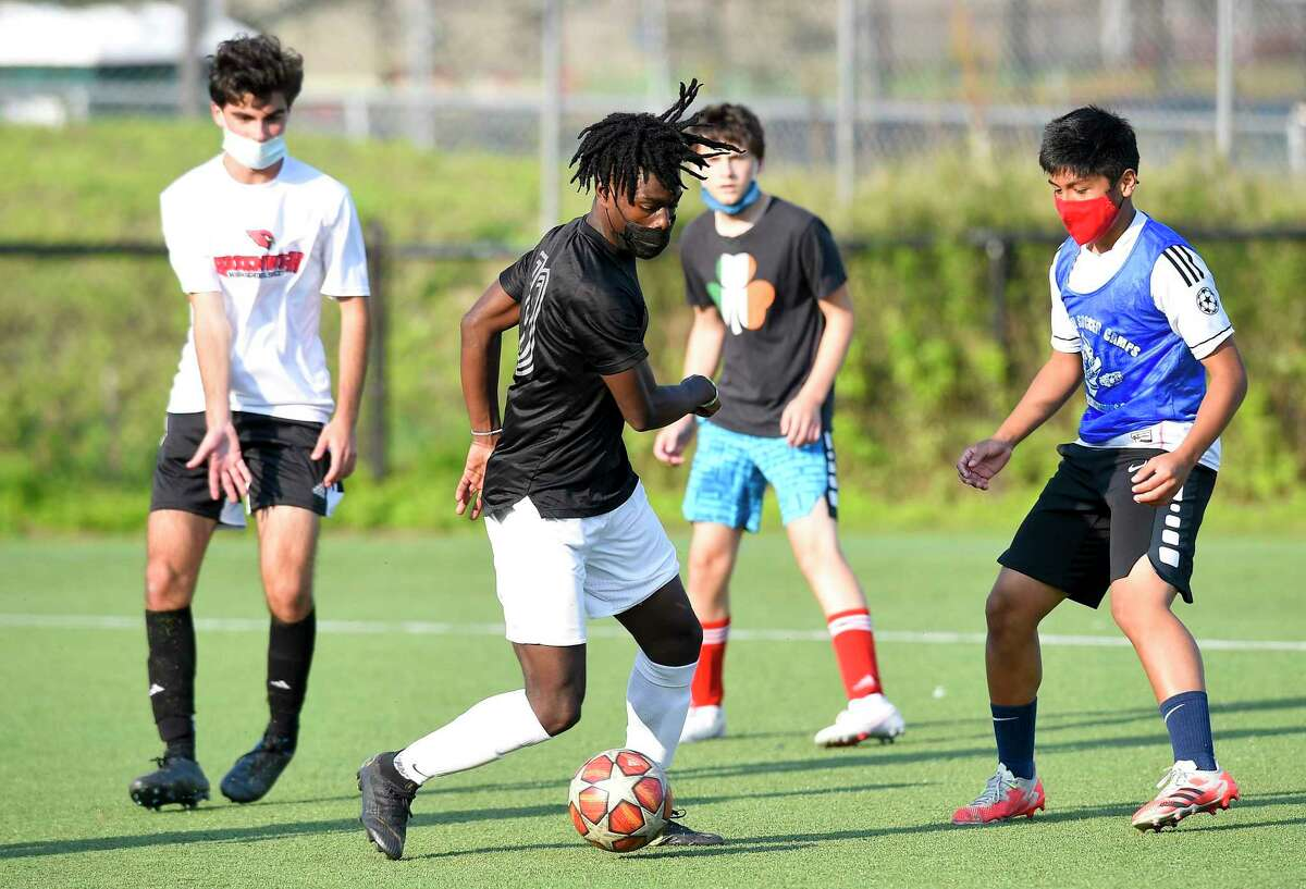 Jeanel Boone, second from left, wears a protective face covering while participating in soccer practice in Greenwich, Connecticut on Sept. 21, 2020.