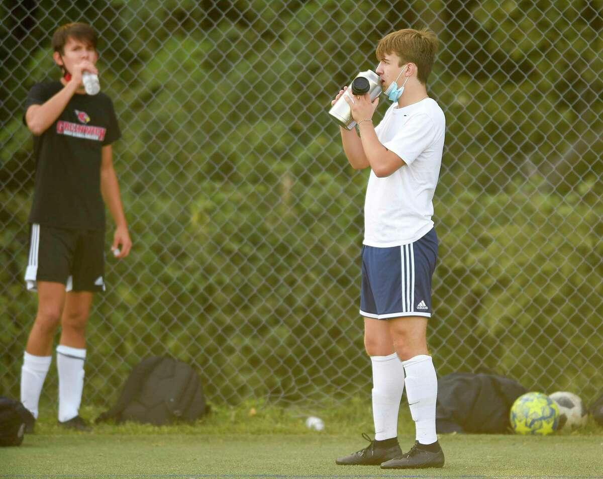 Ryan Smith, at right, lowers his protective face covering to get a drink of water while participating in soccer practice.