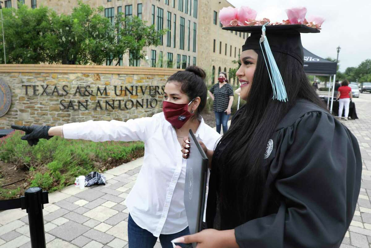 Mariela Lopez, center, directs graduate Lorena Garcia, with pink roses on her cap, to have her picture taken at the curbside graduation ceremony at Texas A&M University San Antonio on May 15.