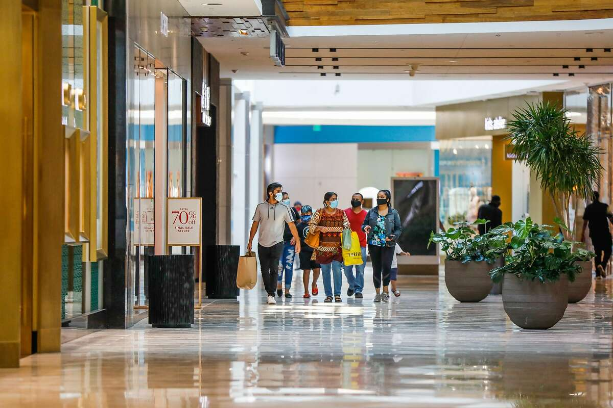 A family shops at Westfield Valley Fair Mall hours after it reopened following the COVID-19 global pandemic in San Jose, California, on Monday, Aug. 31, 2020.