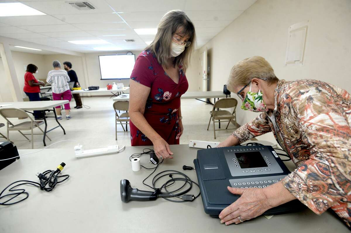 Jefferson County election worker Lynell Landry looks on as Mary Jane Tidwell hooks up a scanner and printer during a training session for those working the polls in the upcoming election. Photo taken Monday, September 21, 2020 Kim Brent/The Enterprise