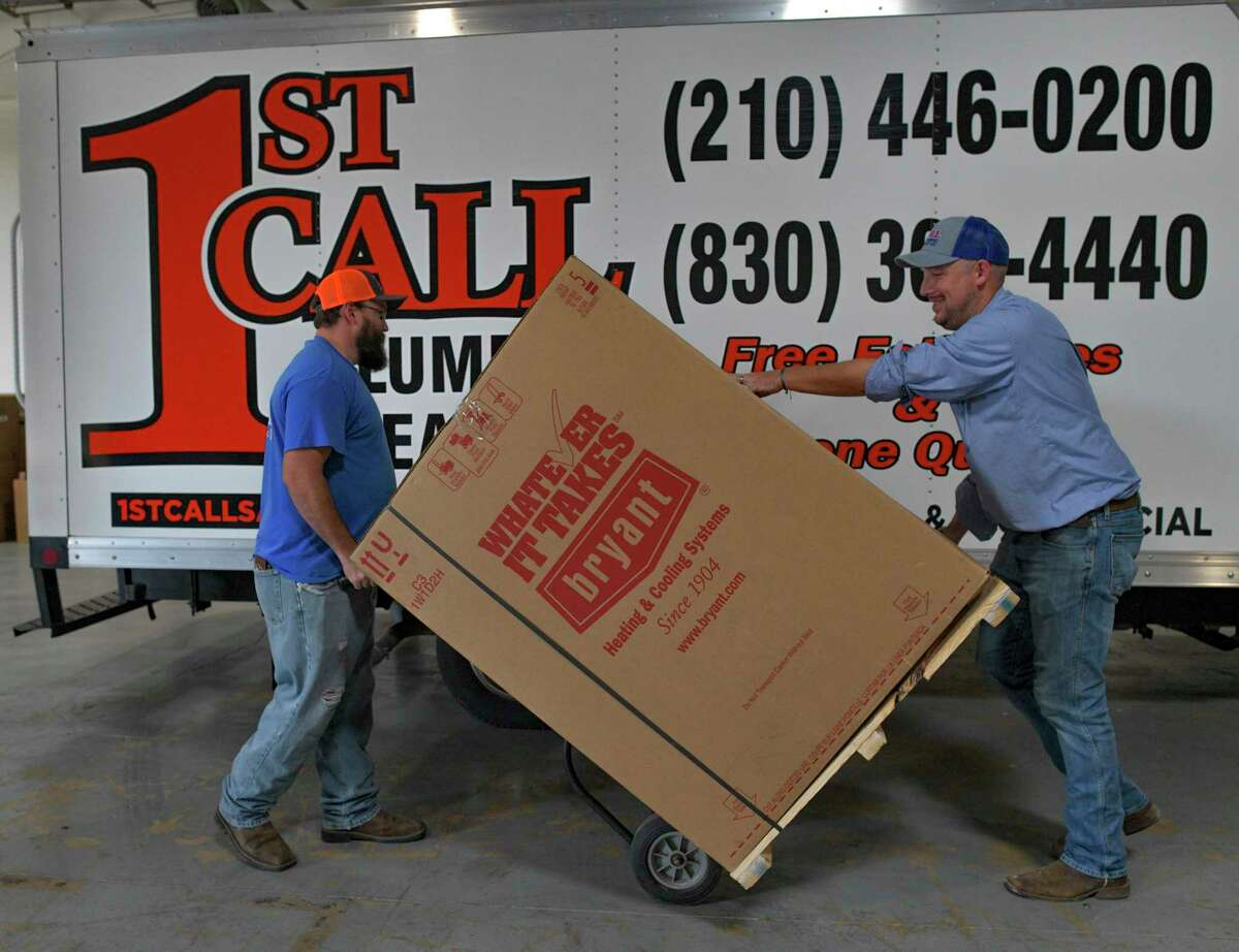 Trey Becker, left, and Ryan Herz handle a Bryant air conditioner unit at 1st Call Plumbing, Heating & Air.