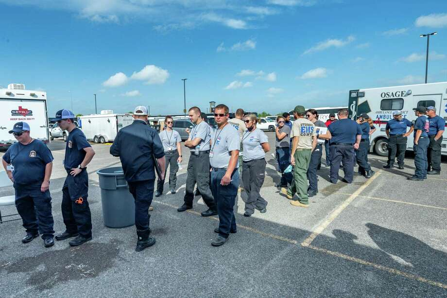 EMS personnel gather around the Southeast Texas Regional Advisory mobile command center to get their assignments. Before winds from Hurricane Laura begin picking up, more than 100 emergency vehicles staged at Ford Park. Photo made on August 26, 2020. Fran Ruchalski/The Enterprise Photo: Fran Ruchalski, The Enterprise / The Enterprise / © 2020 The Beaumont Enterprise