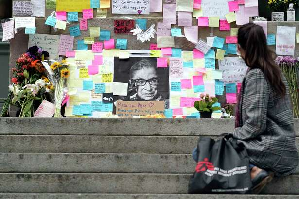A woman sits in front of a memorial to U.S. Supreme Court Justice Ruth Bader Ginsburg on Tuesday outside the Harvard Law School library in Cambridge, Mass.