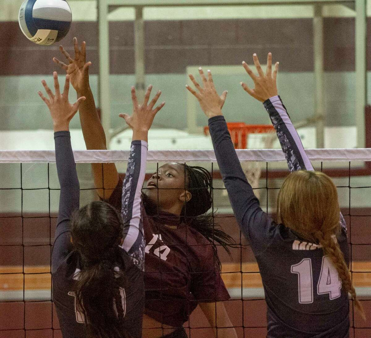 Lee High's Loredana Fouonji tips the ball past the reach of Canyon Randall's Desiree Sotelo and Julia Woolsey 09/22/2020 at the Lee High gym. Tim Fischer/Reporter-Telegram