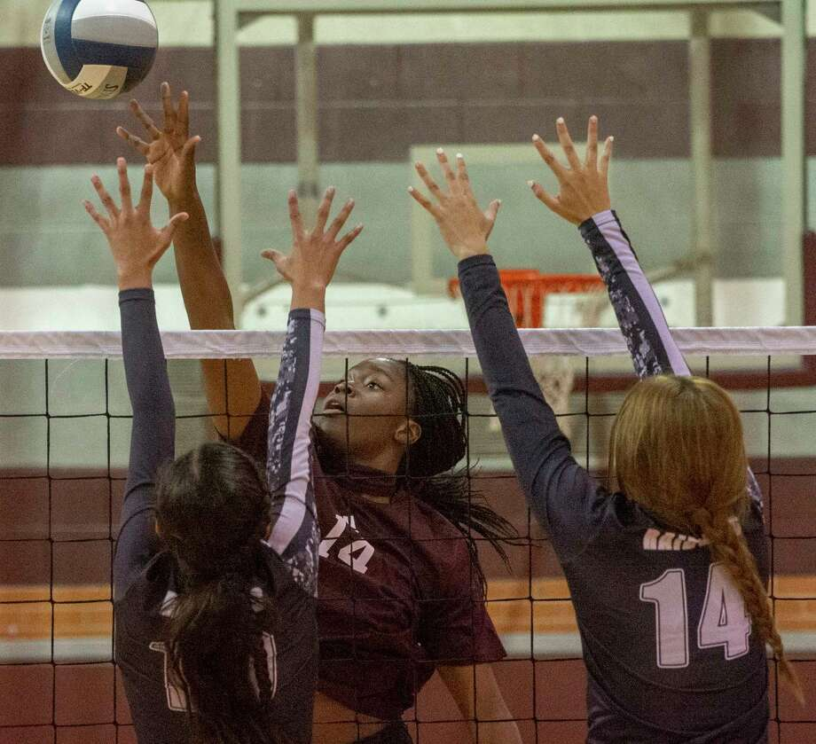 Lee High's Loredana Fouonji tips the ball past the reach of Canyon Randall's Desiree Sotelo and Julia Woolsey 09/22/2020 at the Lee High gym.  Tim Fischer/Reporter-Telegram Photo: Tim Fischer, Midland Reporter-Telegram