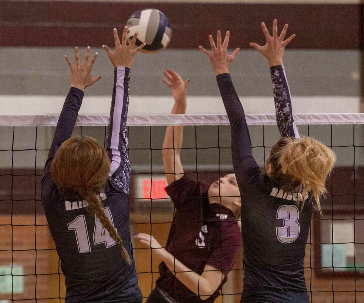 Lee High's Kaitlyn Paredez looks to hit between Canyon Randall's Julia Woolsey and Kylee Williams 09/22/2020 at the Lee High gym. Tim Fischer/Reporter-Telegram