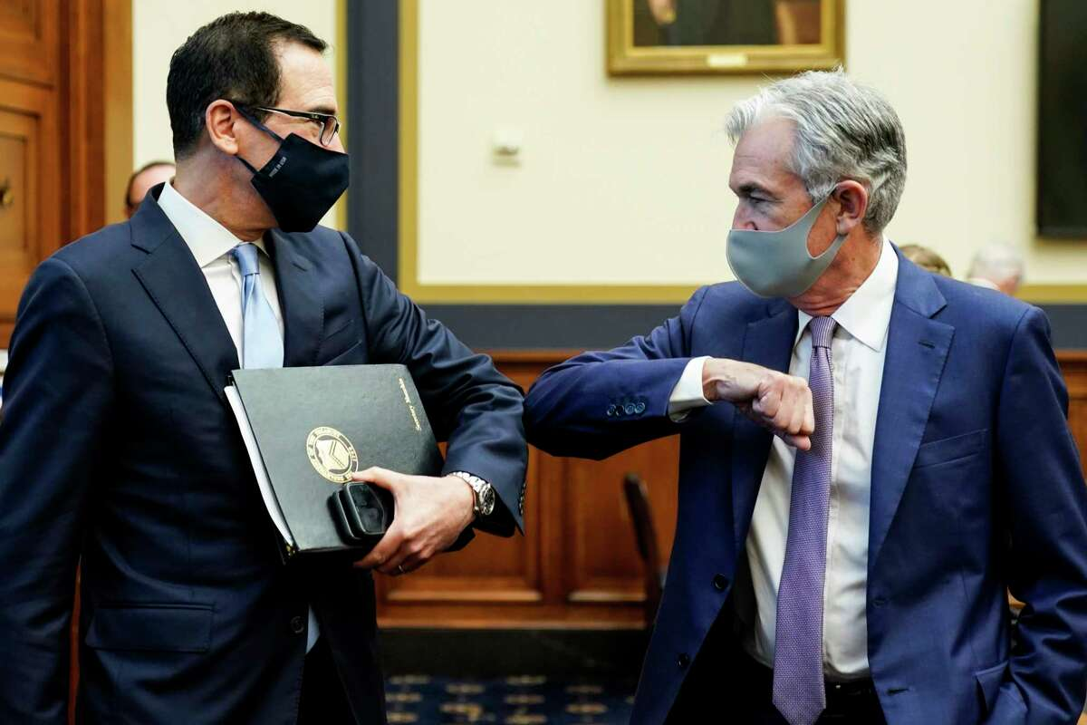 Treasury Secretary Steven Mnuchin, left, greets Federal Reserve Chair Jerome Powell with an elbow bump before the start of a House Financial Services Committee hearing about the governmenta€™s emergency aid to the economy in response to the coronavirus on Capitol Hill in Washington on Tuesday, Sept. 22, 2020. (Joshua Roberts/Pool via AP)