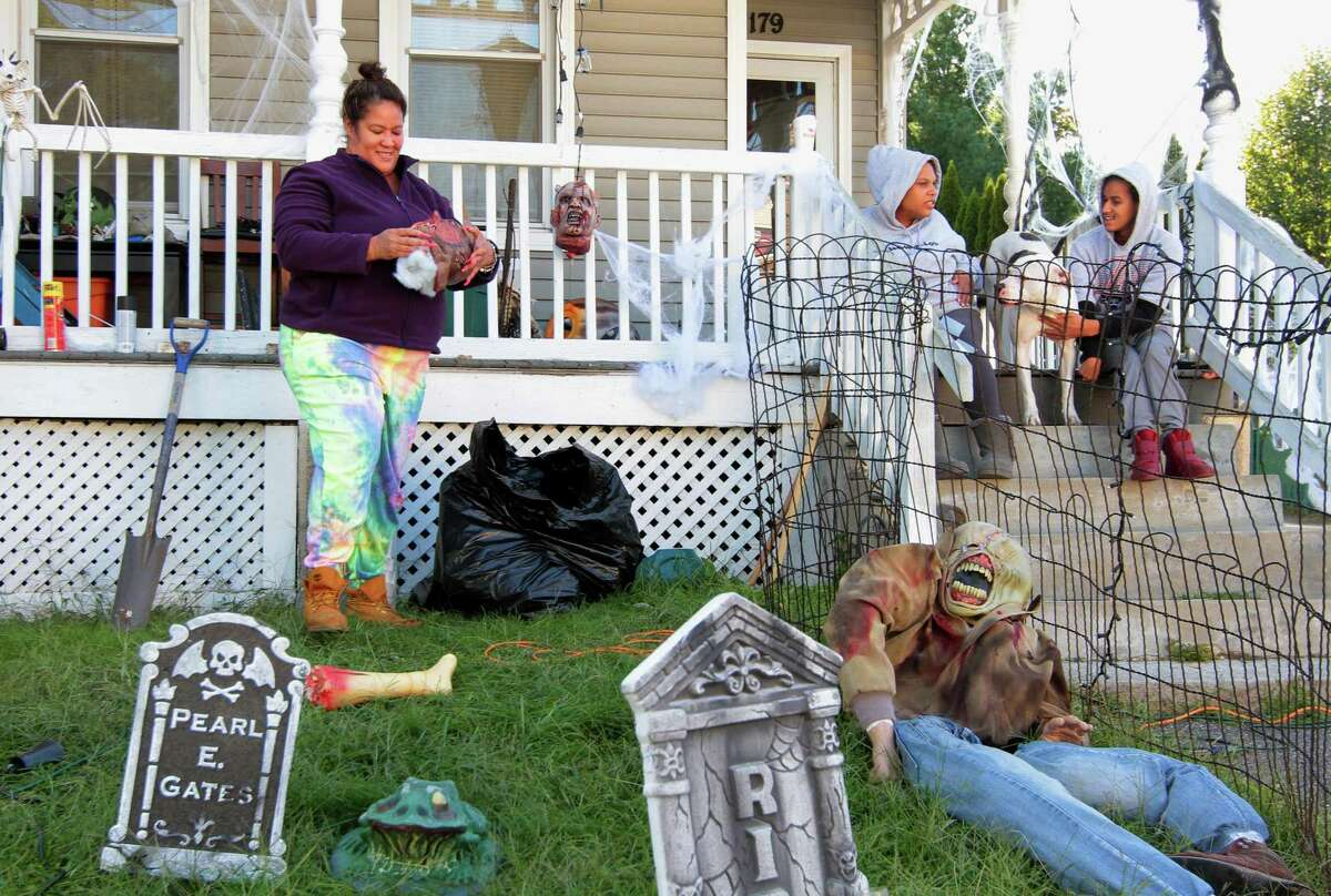Chanel Owens sets up Halloween decorations in front of her home on Howard Avenue in Ansonia, Conn., on Tuesday Sept. 22, 2020. Looking on is friend Tiffany Jackson, Chanel's son Justin, and their dog Bishop.