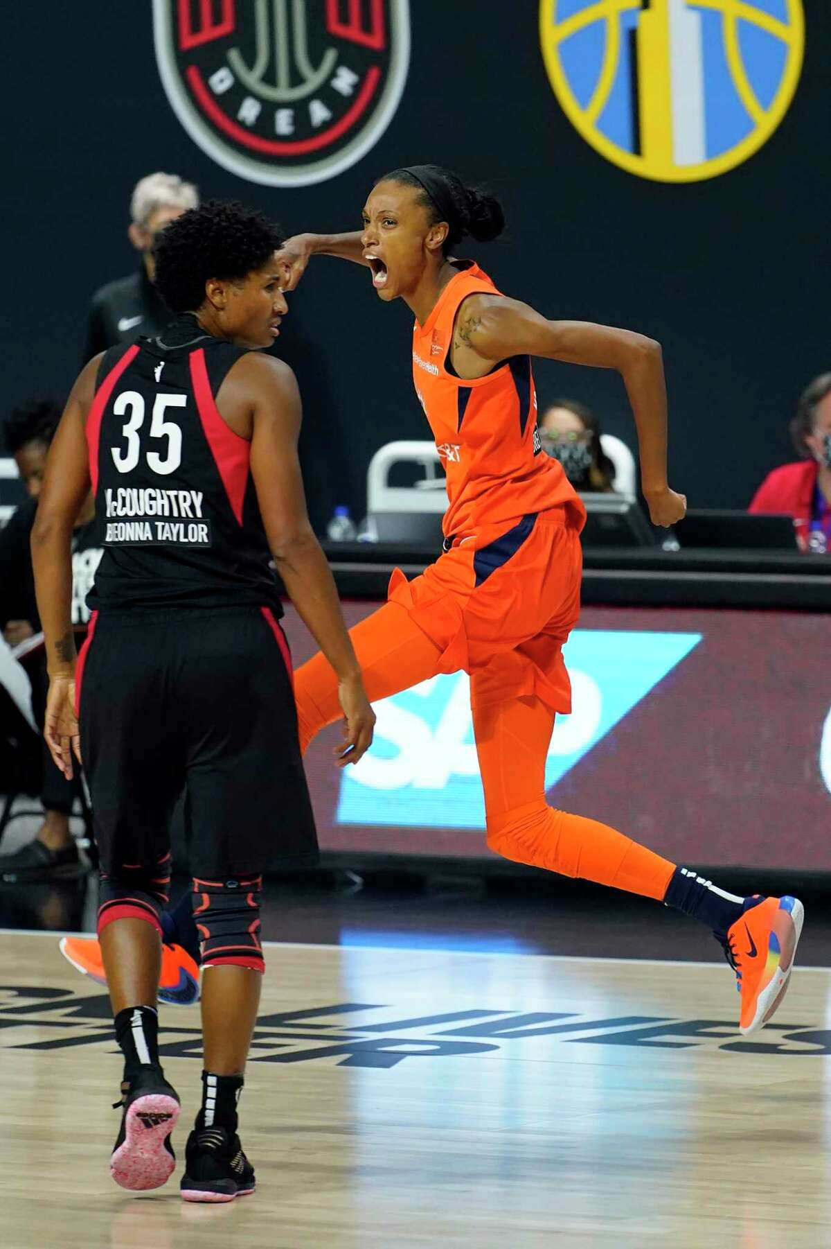Connecticut Sun forward DeWanna Bonner (24) celebrates in front of Las Vegas Aces forward Angel McCoughtry (35) after making a three-point shot during the second half of Game 2 of a WNBA basketball semifinal round playoff game Tuesday, Sept. 22, 2020, in Bradenton, Fla. (AP Photo/Chris O'Meara)