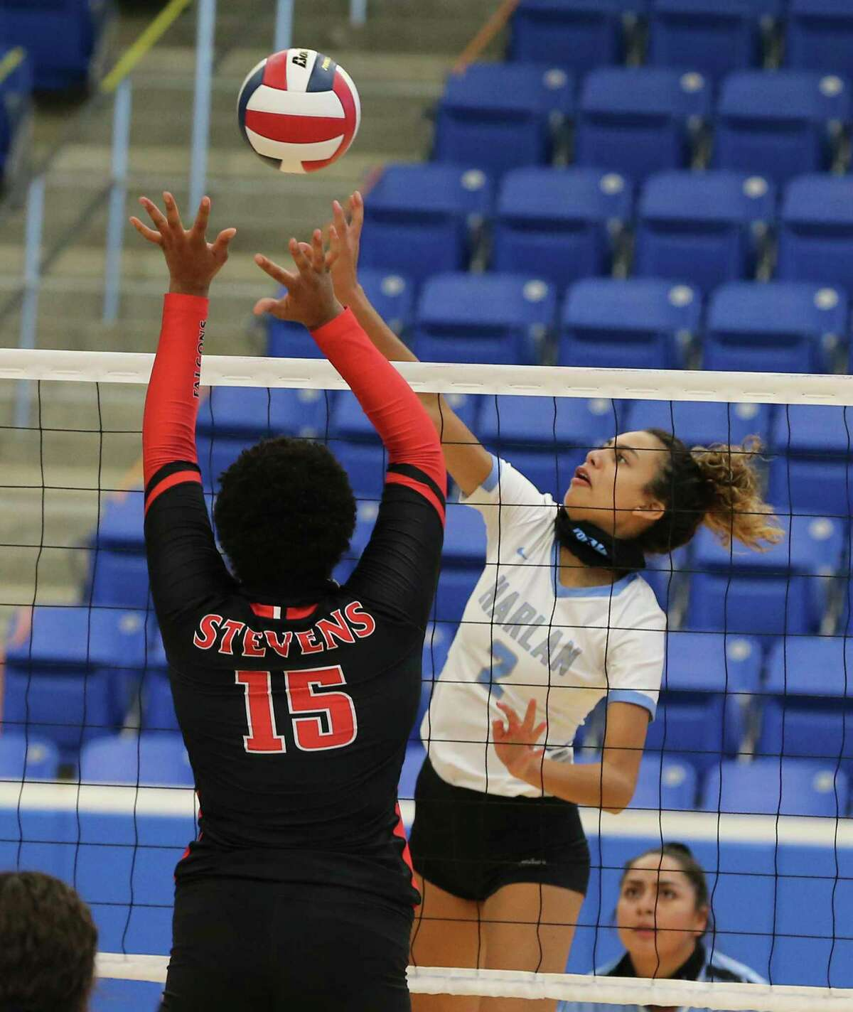 Harlan's Dahlia De Los Santos (02) pushes a shot away from Stevens' Nariah Lee (15) during girls volleyball at Northside Sports Gym on Tuesday, Sept. 22, 2020.