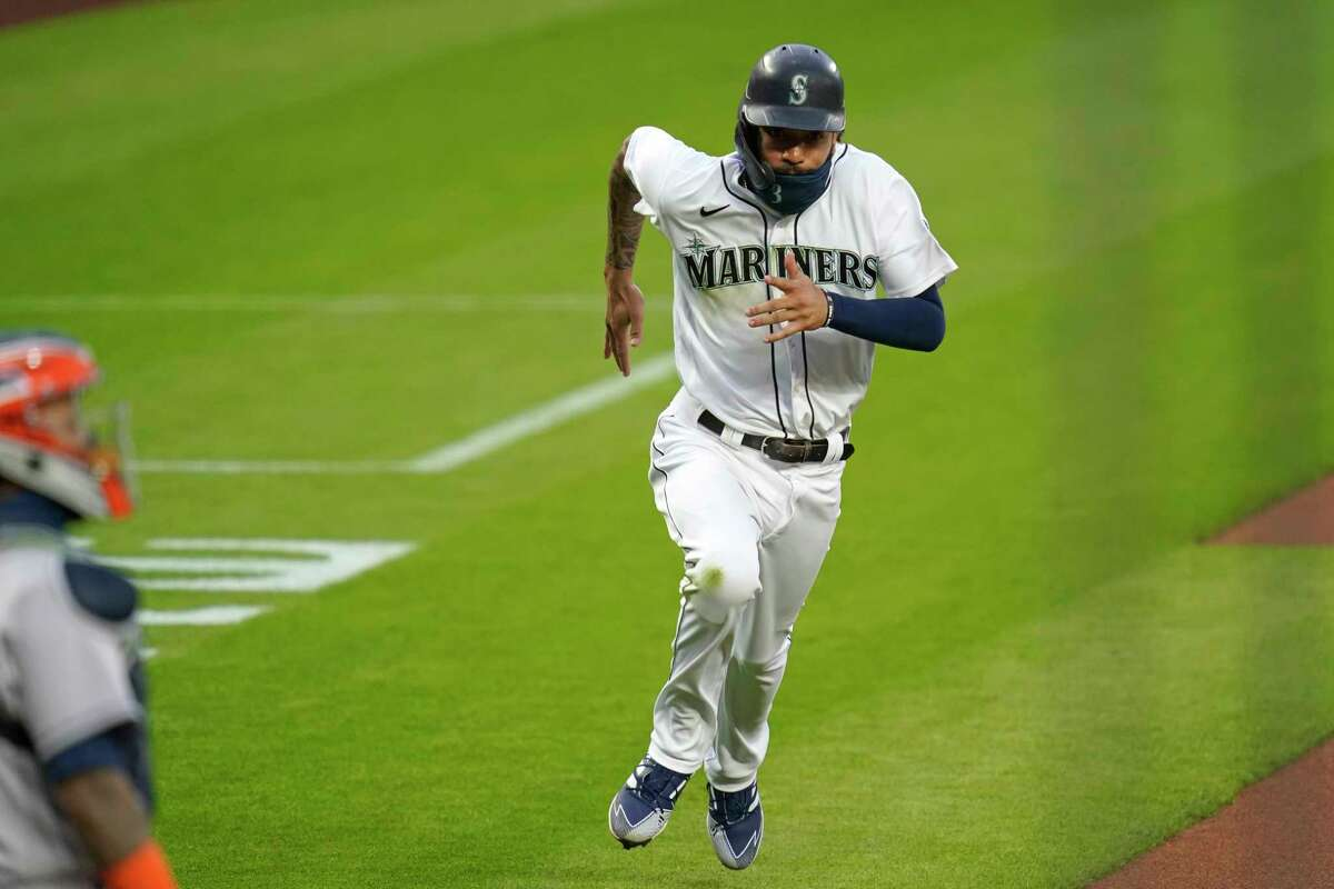 Seattle Mariners' J.P. Crawford races home to score as Houston Astros catcher Martin Maldonado looks on in the first inning of a baseball game Tuesday, Sept. 22, 2020, in Seattle. (AP Photo/Elaine Thompson)