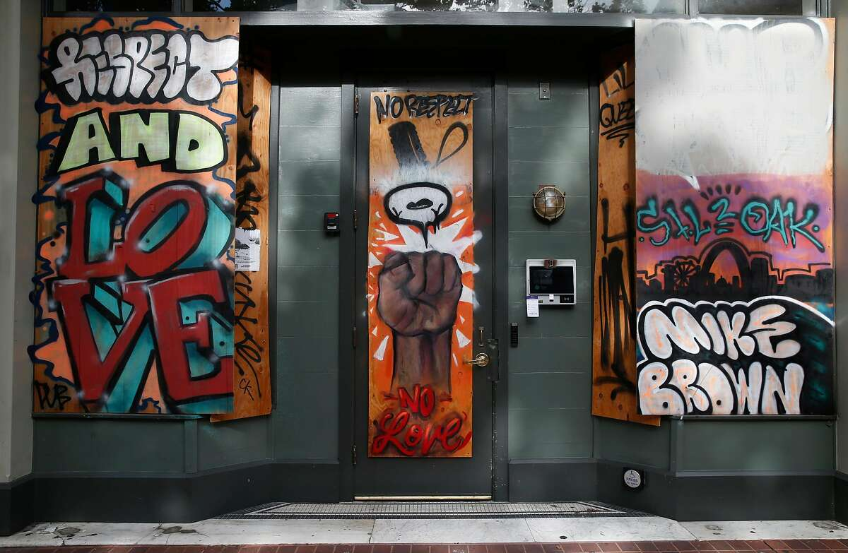 A mural adorns plywood covering the windows at 969 Broadway in Oakland.