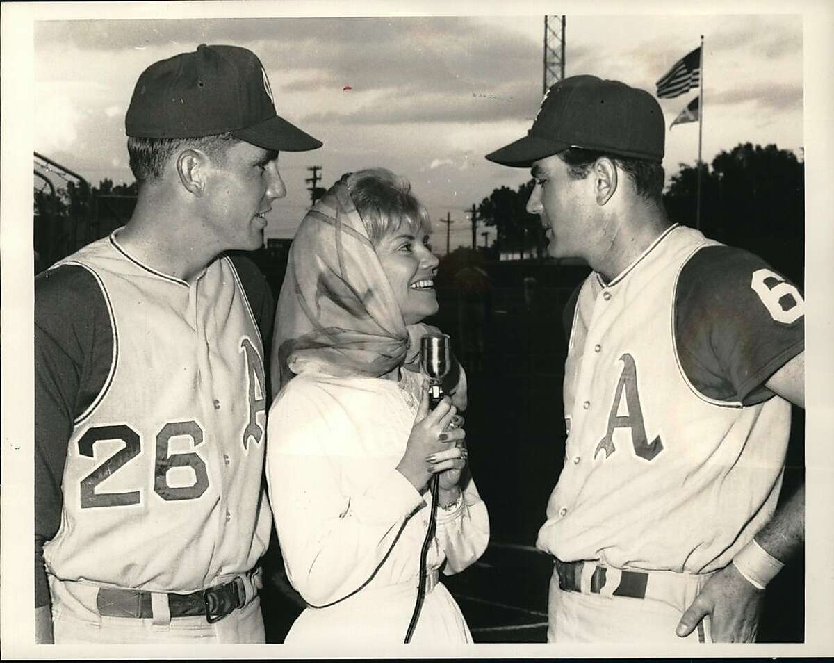 """New voice on baseball - Major league baseball's first woman broadcaster, Betty Caywood, talks with Athletics' pitcher John O'Donoghue (left) and first baseman Jim Gentile during pre-game warmups at Kansas City Municipal Stadium. Miss Caywood does not do the play-by-play but hopes to break into that job in a couple of seasons. She took the job with Kansas City team """"Because it pays good,"""" not because she wanted to break down any barriers to women in the field."""