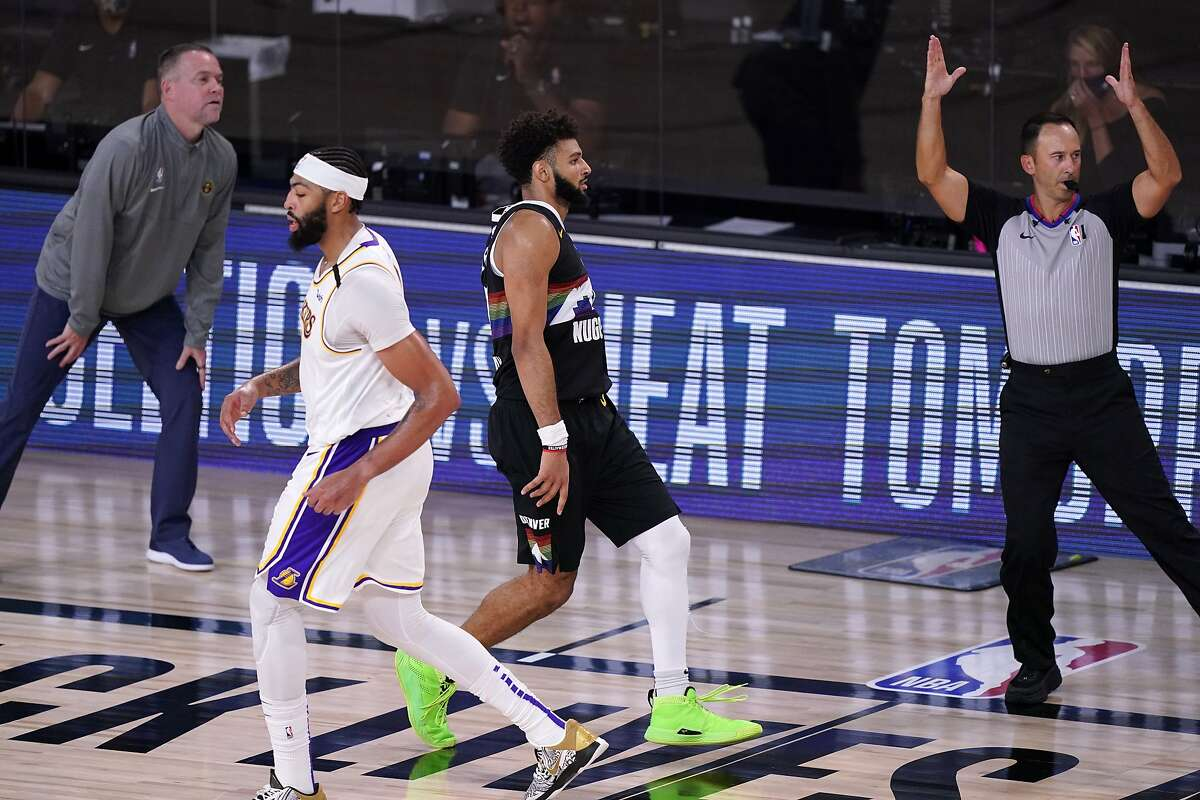 Denver Nuggets guard Jamal Murray, center, celebrates sinking a 3-point basket in front of Los Angeles Lakers' Anthony Davis, center left, as head coach Michael Malone, left, looks on during the second half of Game 3 of the NBA basketball Western Conference final Tuesday, Sept. 22, 2020, in Lake Buena Vista, Fla. (AP Photo/Mark J. Terrill)