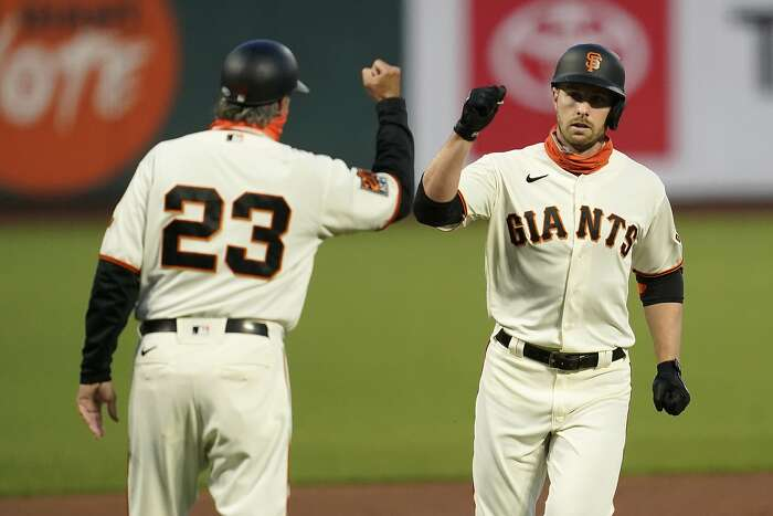 San Francisco Giants' Austin Slater, right, celebrates with third base coach Ron Wotus after hitting a solo home run against the Colorado Rockies during the first inning of a baseball game in San Francisco, Tuesday, Sept. 22, 2020. (AP Photo/Jeff Chiu)
