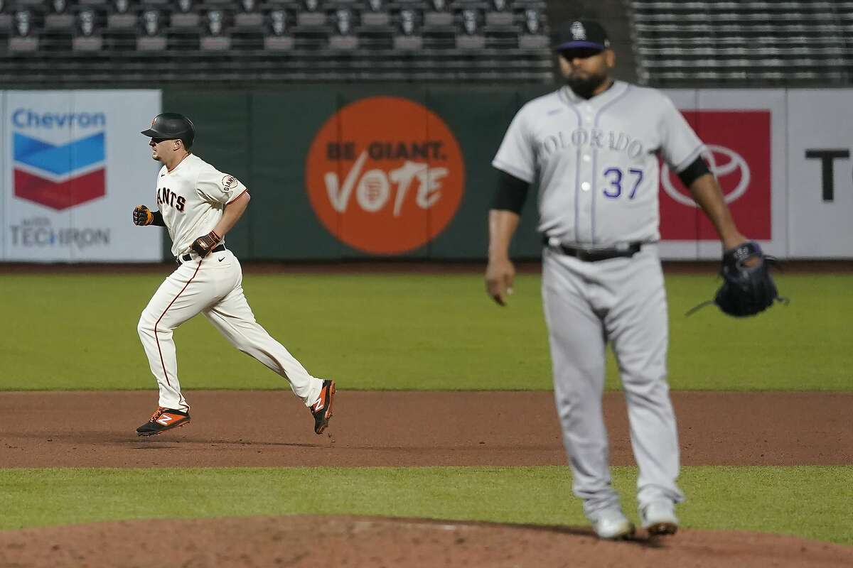 San Francisco Giants' Alex Dickerson, left, runs the bases after hitting a solo home run off Colorado Rockies relief pitcher Jairo Diaz, right, during the seventh inning of a baseball game in San Francisco, Tuesday, Sept. 22, 2020. (AP Photo/Jeff Chiu)